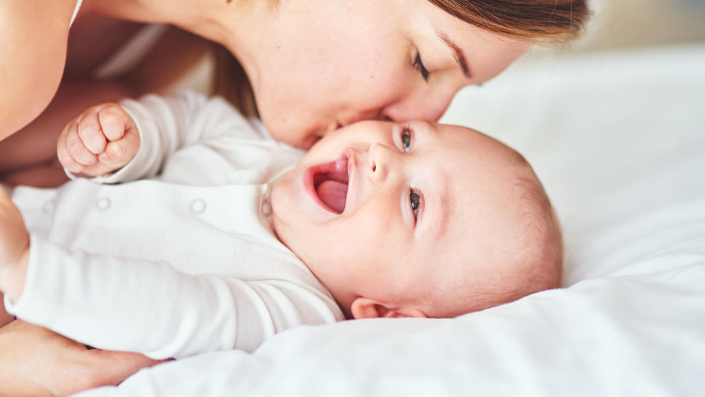 Mutter küsst ihr lachendes Baby