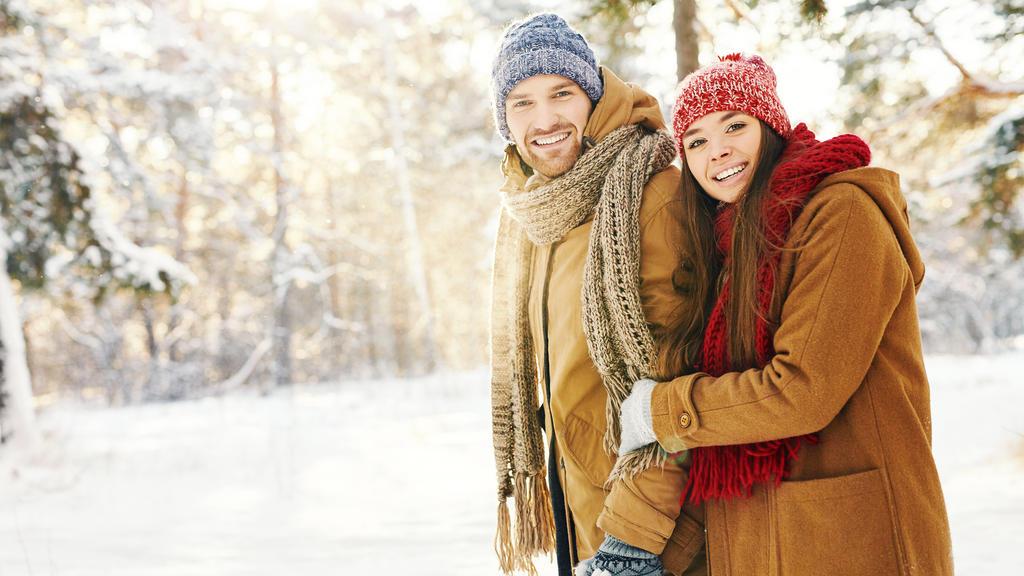 Ein glückliches Pärchen, eingepackt in wintertauglicher Kleidung, bei einem Winterspaziergang im Schnee.