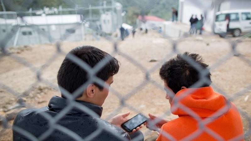Flüchtlinge sitzen in dem Flüchtlingscamp Moria auf der griechischen Insel Lesbos hinter einem Zaun. Moria gilt als einer der größten Flüchtlings-Hotospots in Griechenland.