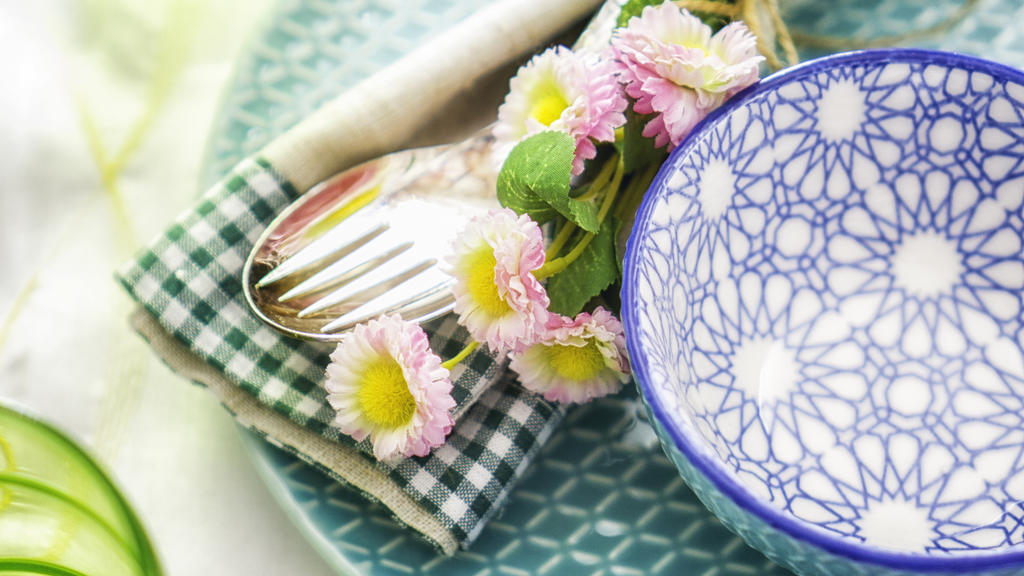 Colorful decorated Easter Place Setting with Easter Eggs, flowers on the table