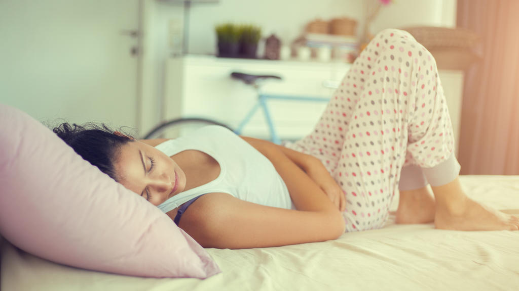 young woman laying in bed and having stomachache