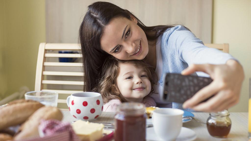 Portrait of mother and her little daughter taking a selfie at breakfast table model released Symbolfoto property released PUBLICATIONxINxGERxSUIxAUTxHUNxONLY HAPF000125Portrait of Mother and her Little Daughter Taking a Selfie AT Breakfast Table Mode