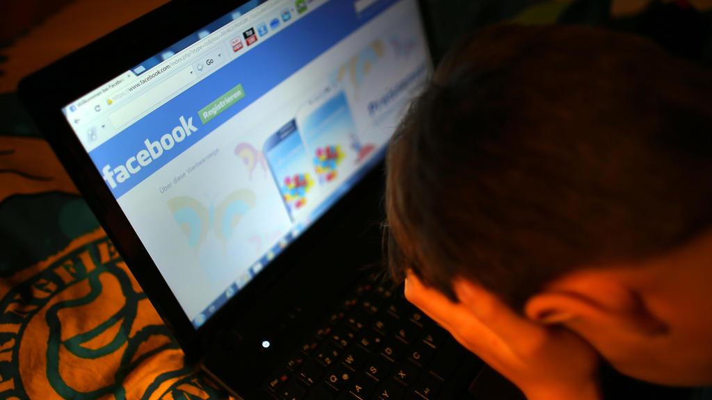 ARCHIV - ILLUSTRATION - Ein Junge reibt sich am 15.05.2013 in Leichlingen (Nordrhein-Westfalen) vor seinem Laptop beim Betrachten der Facebook- Seite die Augen. (zu dpa «Hass im Netz erreicht vor allem die Jungen» vom 30.05.2017) Foto: Oliver Berg/dp