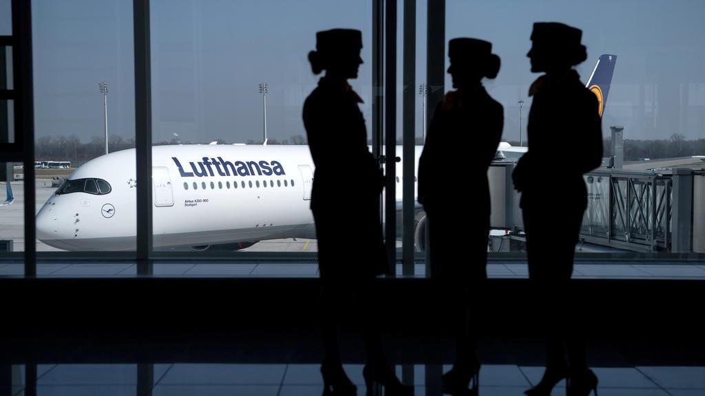 ARCHIV - Flugbegleiterinnen der Deutschen Lufthansa AG stehen am 16.03.2017 am Flughafen in München (Bayern) während der Bilanz Pressekonferenz der Deutschen Lufthansa AG vor einem Fenster am Terminal. (zu dpa «Hauptversammlung der Lufthansa ohne gro