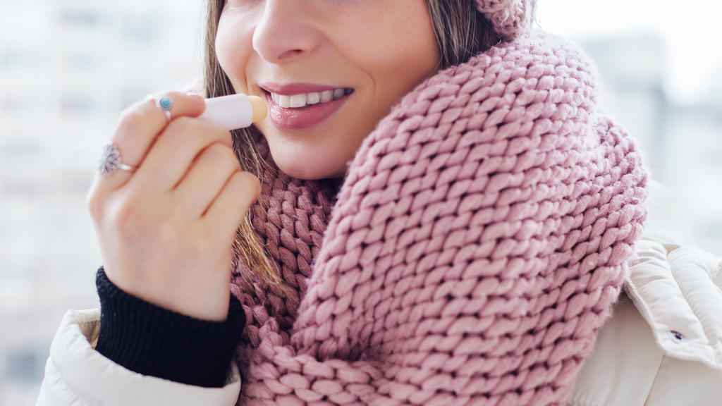 Young women apply lip care balm outside, on cold weather