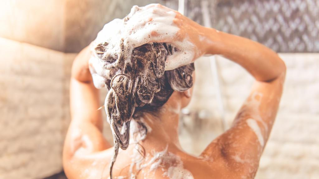 Frau schamponiert sich die Haare unter der Dusche