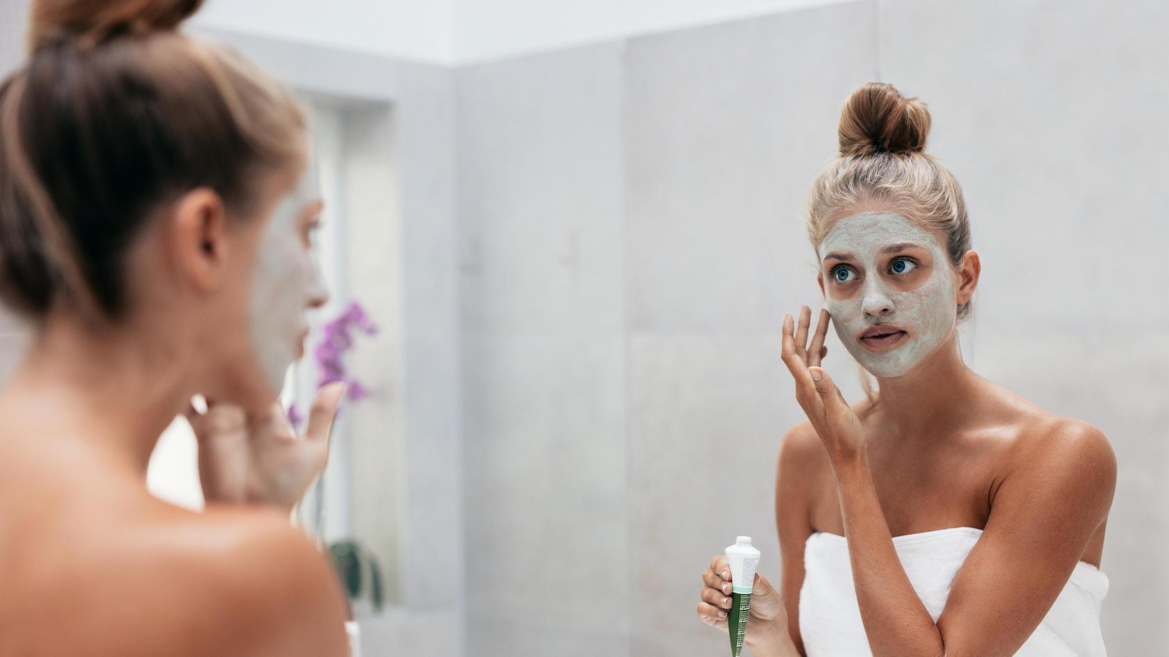 Schöne Frau trägt Maske auf Gesicht auf