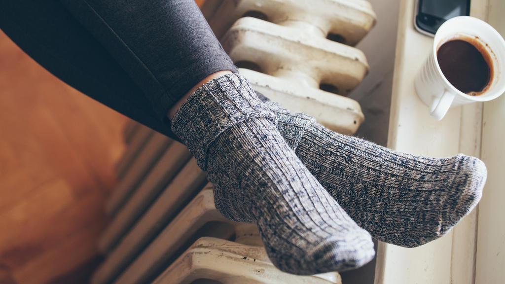 Eine Frau hält ihre Füße auf die Heizung.