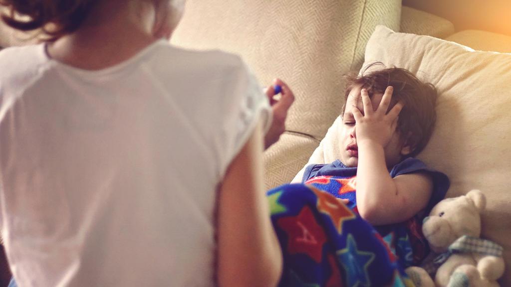 Eine Mutter hat bei ihrem Kind, das offensichtlich erkältet ist, Fieber gemessen.