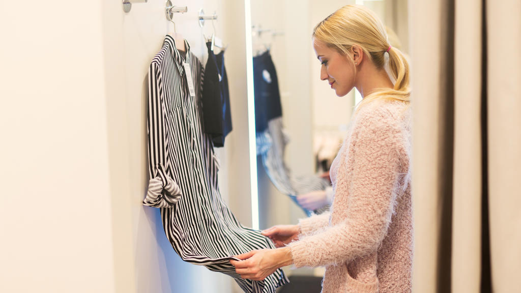 Elegant young woman is  in a fitting room of a fashion store trying on some clothes. Side view.
