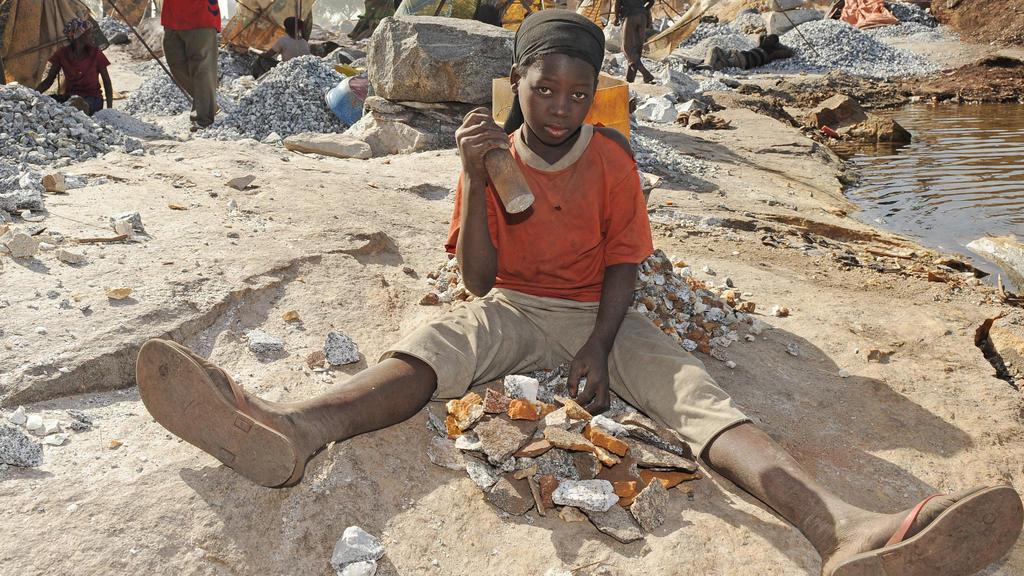 ARCHIV- Die 14-jährige Ibudo Asseta arbeitet im Steinbruch Pissy in Ouagadougou in Burkina Faso und zerkleinert mit einem Metallkolben Granitsteine (Aufnahme vom 06.11.2009). Sie ist seit zwei Jahren nicht mehr zur Schule gegangen, weil sie arbeiten