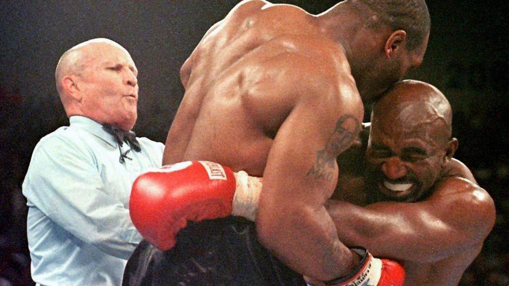 Mit einem der größten Skandale der Boxgeschichte endet am 28.6.1997 in Las Vegas der Rückkampf zwischen Schwergewichts-Weltmeister Evander Holyfield (r.) und Mike Tyson M./beide USA). Ringrichter Lane Mills (l.) geht dazwischen, nachdem Tyson Holyfie