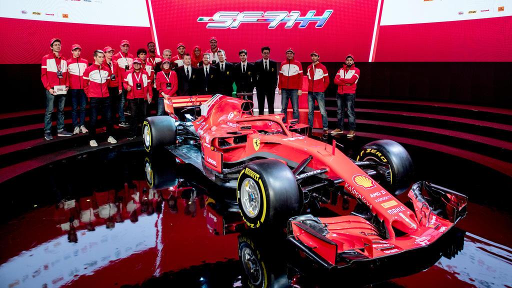 HANDOUT - 22.02.2018, Italien, Maranello: Vorstellung des neuen Ferrari  SF71H mit Sebastian Vettel (M, 2.v.l) und dem Ferrari-Team. Ferrari lüftete als letztes der drei Top-Teams der Formel 1 das Geheimnis um den neuen Rennwagen. (zu dpa Formel 1 le