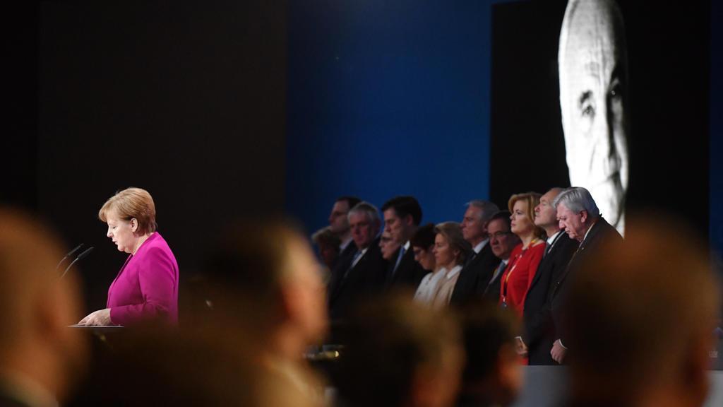 26.02.2018, Berlin: Bundeskanzlerin Angela Merkel (CDU) am Rednerpult während des Gedenkens an den verstorbenen ehemaligen Bundeskanzler Helmut Kohl (r) beim 30. Parteitag der Christlich Demokratischen Union Deutschlands (CDU). Fot