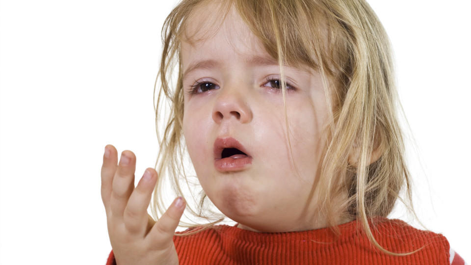 A little girl has a cold and coughs in her hand.