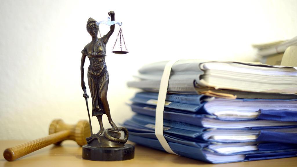 ARCHIV- ILLUSTRATION- Eine modellhafte Nachbildung der Justitia steht am 15.07.2014 im Raum eines Richters des Landgerichts Duisburg (Nordrhein-Westfalen) neben einem Holzhammer und einem Aktenstapel. Im Landgericht Bochum sollen Richter nun das Ur