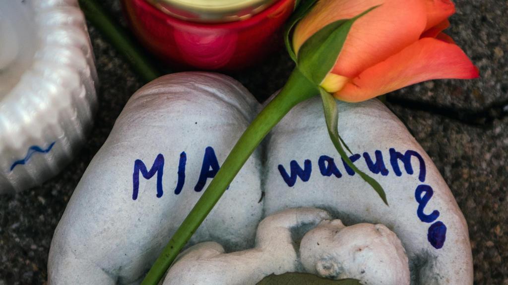 """ARCHIV - 28.12.2017, Rheinland-Pfalz, Kandel: Eine Skulptur in Form zweier Handflächen mit der Aufschrift """"Mia warum?"""" und eine Rose liegen vor dem Drogeriemarkt, in dem ein 15-jähriges Mädchen von ihrem Ex-Freund erstochen wurde.  (zu dpa «Mordankla"""