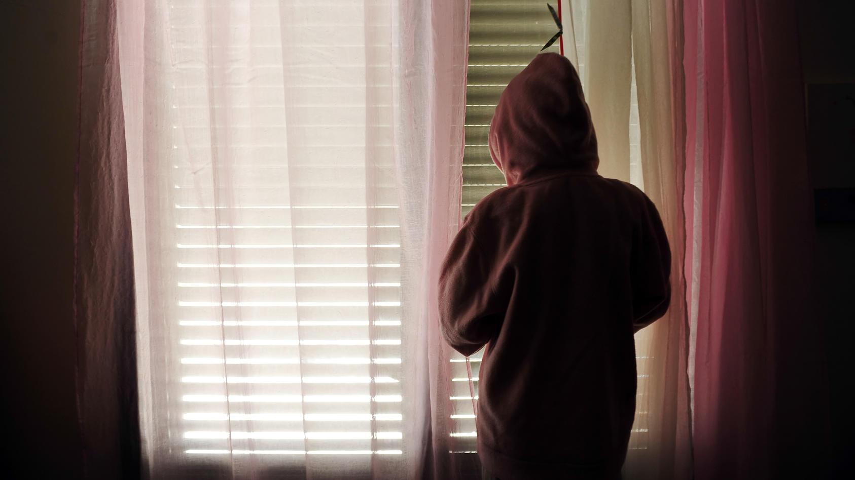 Junges Mädchen steht traurig am Fenster.