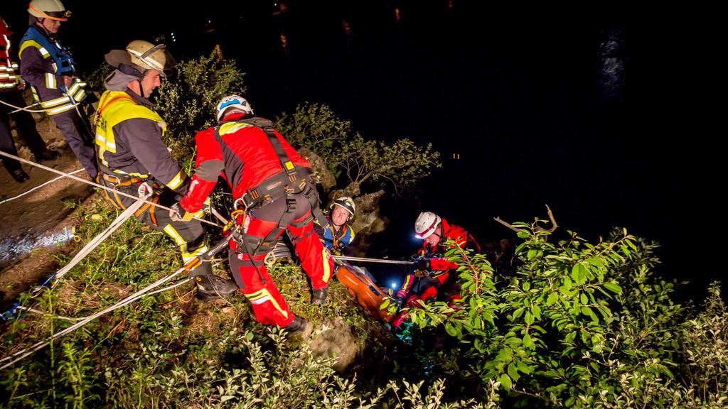 21.05.2018, Rheinland-Pfalz, Sankt Goarshausen: Rettungskräfte und Einsatzkräfte der Feuerwehr bergen einen Mann aus einer Feldwand. Ein 31-Jähriger hat sich bei einem 15 bis 20 Meter tiefen Sturz vom Loreleyfelsen einen Schulterbruch und etliche Pre